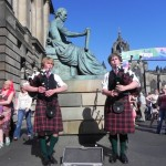 two handsome pipers on high street with st giles cathedral in the background