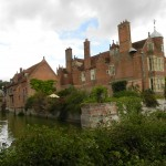 a side view of kentwell hall and moat