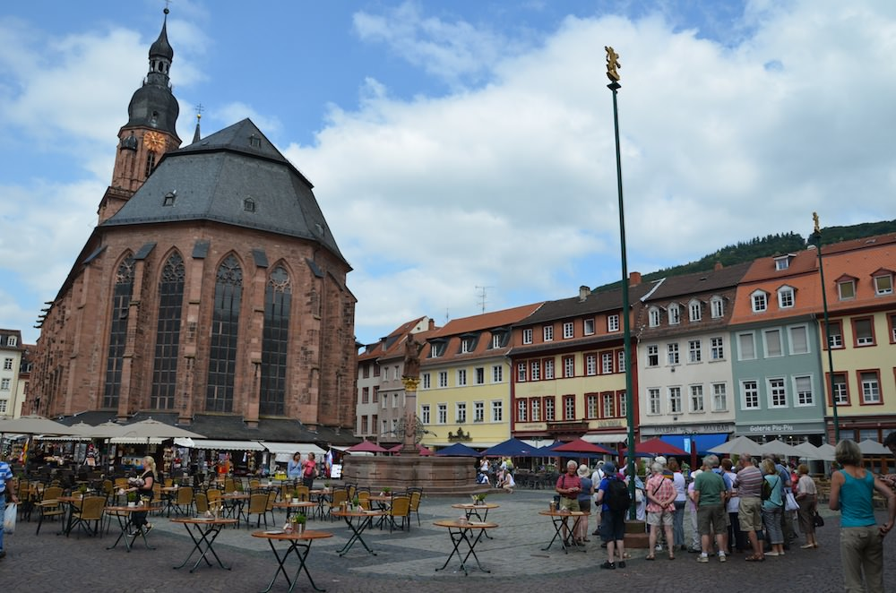 A red sandstone baroque church, the Heiliggeistkirche, looks somberly down on the square.