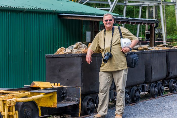 The author stands beside an ore cart loaded with ore from the gold mines.