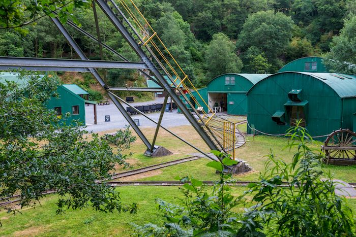 This picture shows the green buildings, ore carts, and gravel courtyard at the Dolaucothi gold mines.