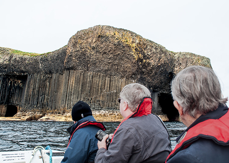 Approaching from the sea, Staffa looks a bit like muffins tipped at an angle. The slow cooling of the lava formed basalt columns below that overflowed in a jumble on top. Fingal's Cave is on the right.