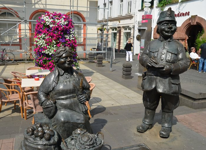 Bronze Statues of a Jolly, Rotund Policeman Standing Next to a Market Wife.