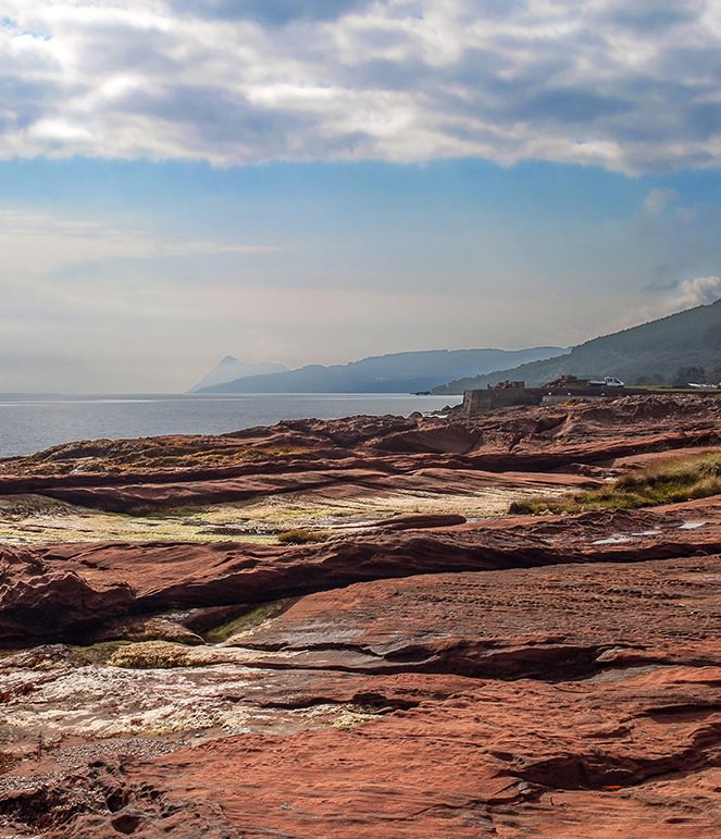 Arran's red sandstone on the east coast has been quarried and used for castles, hotels, and cottages. In the far distance peeking above the mist is Holy Isle, a place of retreat.