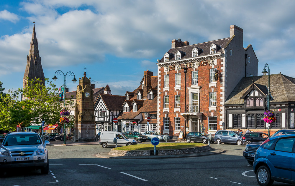 The red brick façade of the Myddelton Arms pub and Castle Hotel on one side and St. Peter's Church nearby make an entrancing place for people watching