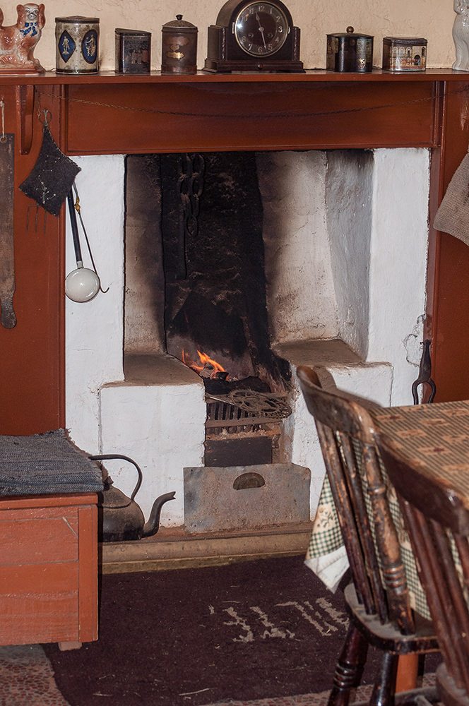 The interior of a blackhouse about 1955. Peat burns hot and slowly, heating the stone walls that radiate it back into the cottage. Long ago, cooking was done over the fire