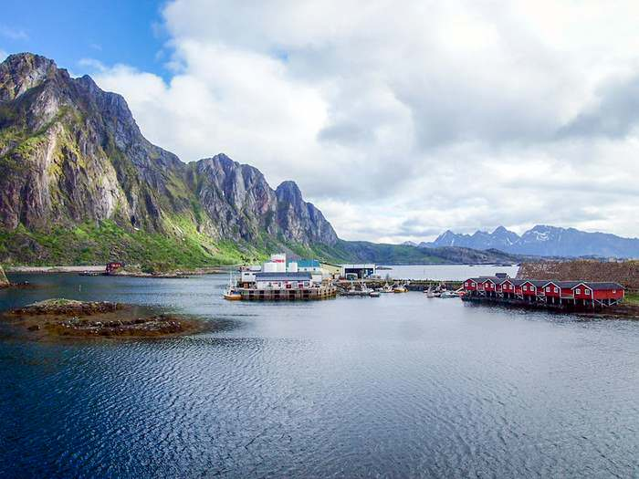 Fishing boats and boat houses backed by sheer mountain ranges in Svolvær