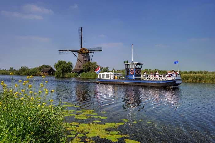 A tourist boat travels past the Kinderdijk windmills